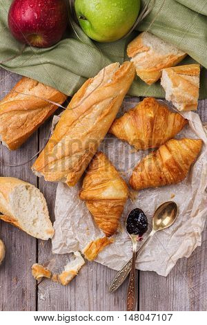 Still life, food and drink concept. French baguette bread with butter and jam and croissant for breakfast on a rustic wooden table. Selective focus, top view overhead flat lay