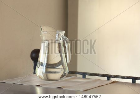 Glass jug with water on a wooden table