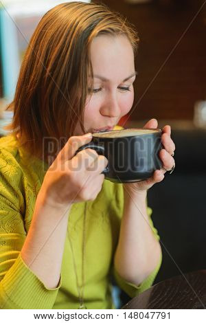 Woman drinking hot coffee at a cafe
