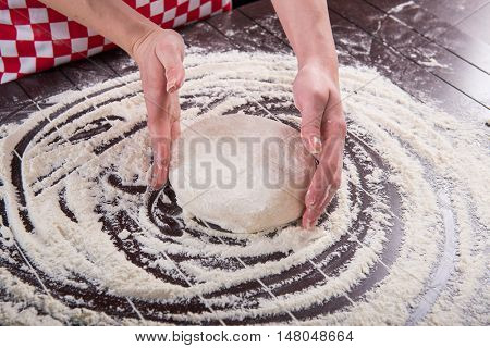 Cook preparing dough for baking in the kitchen