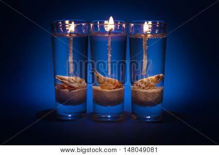 three gel candle with decorative shells in a marine style on a dark blue background