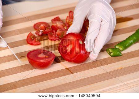 Hands of cook preparing salad