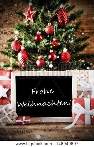 Christmas Card For Seasons Greetings. Christmas Tree With Balls. Gifts Or Presents In The Front Of Wooden Background. Chalkboard With German Text Frohe Weihnachten Means Merry Christmass