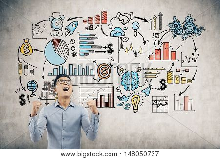 Portrait of Asian businessman standing near concrete wall with startup sketch and shouting with joy. Concept of business success. Toned image