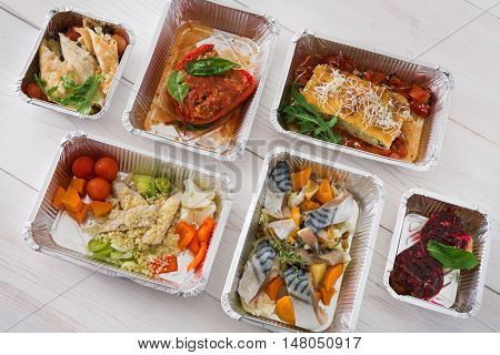 Healthy food delivery, daily ration. Take away of natural organic low carb diet. Fitness nutrition in foil boxes. Top view, Mackerel fish, vegetables and fruits