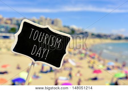 closeup of a black signboard with the text tourism day written in it in front of a blurred crowded beach
