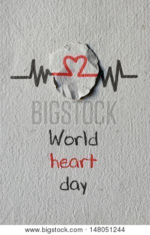 a red heart symbol on a round piece of paper as in an electrocardiogram and the text world heart day written on a textured paper background