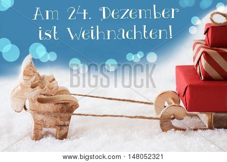Moose Is Drawing A Sled With Red Gifts Or Presents In Snow. Christmas Card For Seasons Greetings. Light Blue Background With Bokeh Effect. German Text Am 24. Dezember Ist Weihnachten Means Christmas