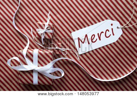 Two Gifts Or Presents With White Ribbon. Red And Brown Striped Wrapping Paper. Christmas Or Greeting Card. Label With French Text Merci Means Thank You