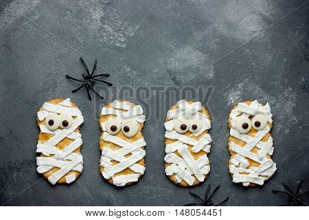 Mummy cookies for Halloween party. Thematic background on Halloween. Creative food idea for kids