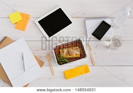 Healthy lunch from take away - foil box with lasagna with water glass and wooden cutlery on table. Restaurant food on office table with mobile phone, papers and tablet. Top view, copy space