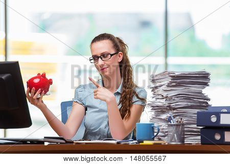 Young businesswoman with piggy bank in the office