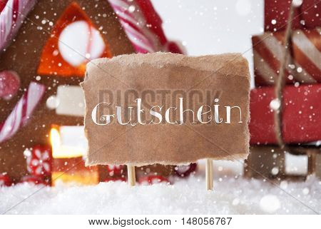 Gingerbread House In Snowy Scenery As Christmas Decoration. Sleigh With Christmas Gifts Or Presents And Snowflakes. Label With German Text Gutschein Means Voucher