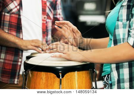 Musicians playing congas in music store. Close up concept.