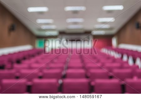 Blurred red seat rows in a bright lecture room.