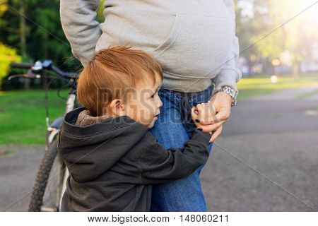 Son embracing his pregnant mother. Mom and baby in anticipation of the newborn. The large family. Pregnant woman and a boy walking in the park.