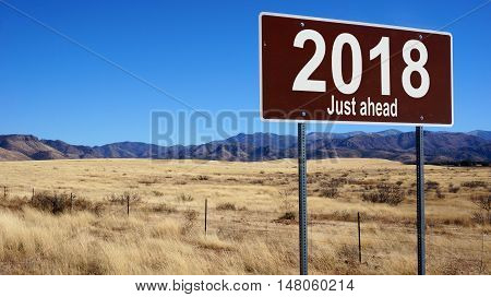 2018 Just Ahead brown road sign with blue sky and wilderness
