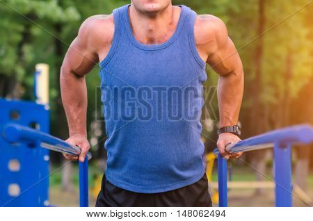 fitness sport exercising training and lifestyle concept - unrecognizable young man doing triceps dip on parallel bars outdoors