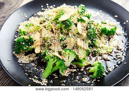 Close-up view of delicious steamed broccoli with garlic chips sprinkled with sesame seeds and dressed with soy sauce and ginger on the black plate. Tasty garnish dish of chinese cuisine. Green food