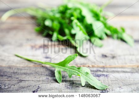Close up view of bunch fresh arugula or rucola or rocket salad leaves on wooden table. Arugula is rich in vitamins and trace elements. Perfect for salads, meat dishes, pasta or sauce pesto. Green food
