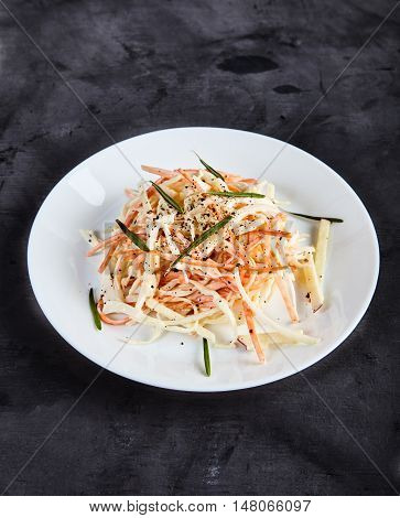 Homemade, crunchy salad coleslaw made the traditional way and decorated with herbs and ground pepper. Shredded carrot, cabbage and Apple, dressed with mayonnaise on white plate. Black background.