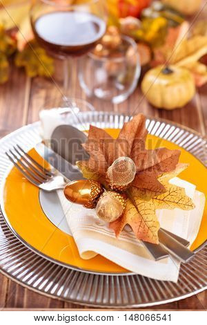 Autumn place setting with leaves candles and pumpkins.