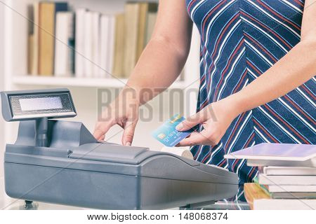 Seller using cash register at bookstore and holding credit card