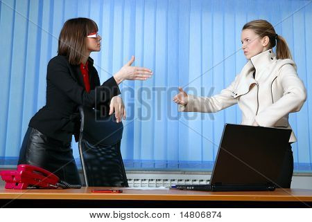 .two businesswomen in suits shaking hands and smiling.