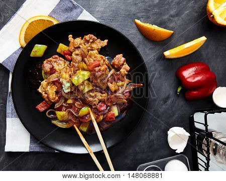 Stir fried chicken with onion, bell pepper, scrambled egg and soy sauce on a black plate with chopsticks. Asian meal on a black background, with a towel, a slice of orange and an egg shell, top view