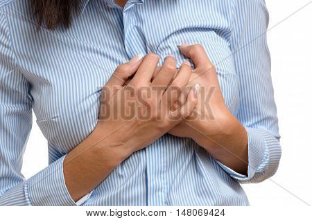 Woman clutching her breast in pain as she suffers the preliminary symptoms of a heart attack or myocardial infarct close up body view isolated on white