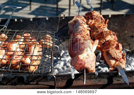Grilled marinated caucasus barbecue meat shashlik (shish kebab) pork meat grilling on metal skewer close up