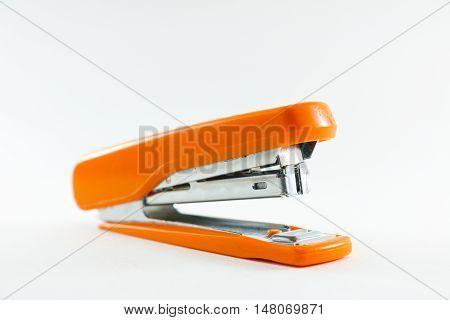 Orange stapler on white background isolated close up.