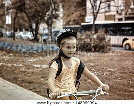 Bikes bicyclist girl. Girls wearing bicycle helmet with rucksack ciclyng bicycle. Buildings at background. Toned image.