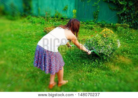 young woman in garden playfully pushing decorative wheelbarrow full of flowers