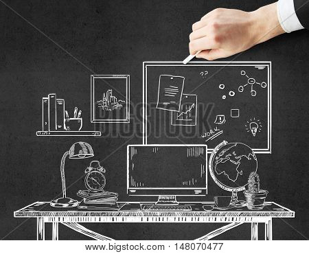 Businessman hand drawing creative office workplace sketch with chalk stick. Concrete background