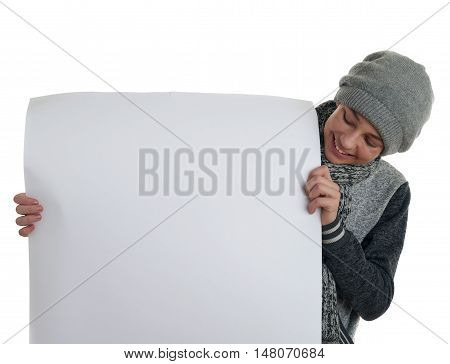 Cute teenager boy in gray sweater, hat and scarf holding paper bill board over white isolated background, half body