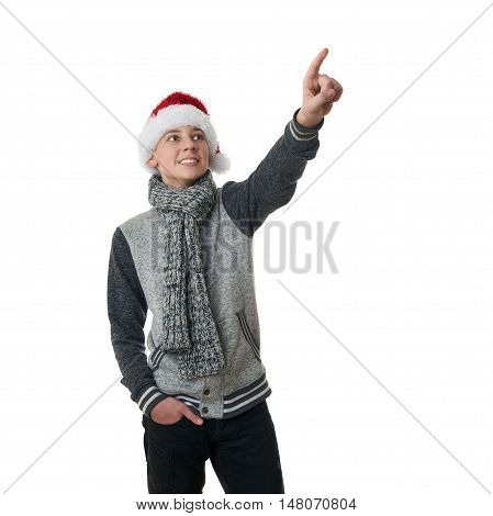 Cute teenager boy in gray sweater and christmas hat pointing up over white isolated background, half body