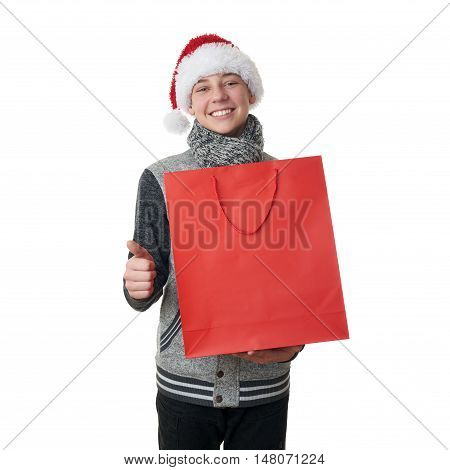 Cute teenager boy in gray sweater and christmas hat holding one red shopping bag over white isolated background, half body