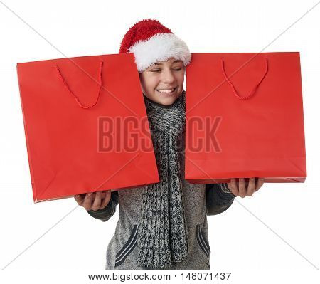 Cute teenager boy in gray sweater and christmas hat holding red shopping bags in two hands over white isolated background, half body