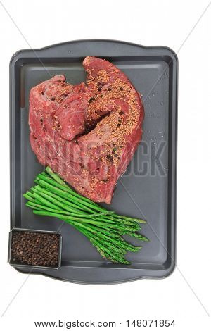 meat raw beef fillet chunk on black tray asparagus allspice isolated on white background empty space for text