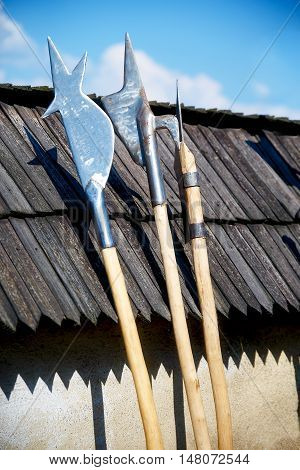 set of middle age style weapons leaning on wooden tiled roof