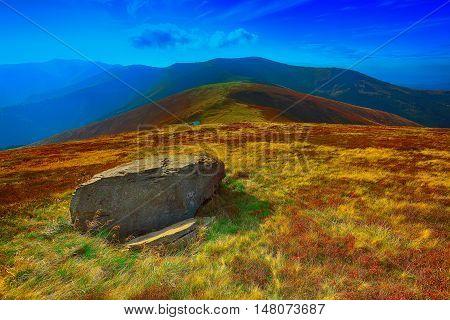 winding road through meadows of mountain range. Big rock at foreground