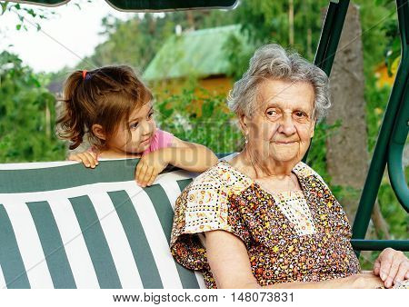 Grandmother with grandchild - senior woman looking at her granddaughter outdoor in nature