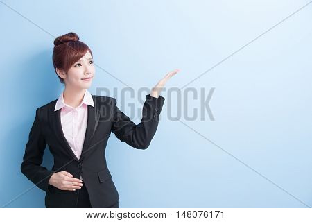 business woman is smile and show something to you with isolated on blue background asian