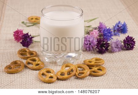 Glass of milk and crackers and with cornflowers. Steklny glass of milk and cookies. A glass of milk with blue flowers.