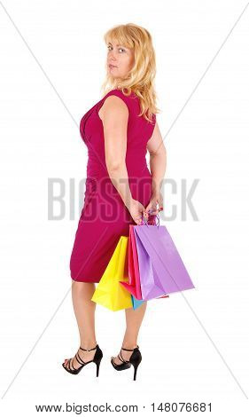 A pretty woman in her forties holding the shopping bag's standing in high heels isolated for white background.