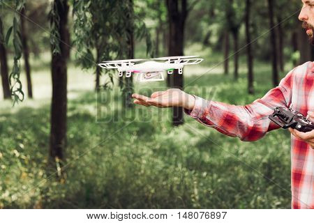 Unrecognizable man running quadrocopter in forest. Review of new unmanned aerial copter outdoor. Aeromodelling hobby, new sample testing