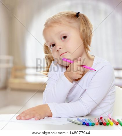 Pretty little blonde girl drawing with markers at the table.The girl thoughtfully looks into the camera.The concept of pre-school education of the child among their peers . in gaming room