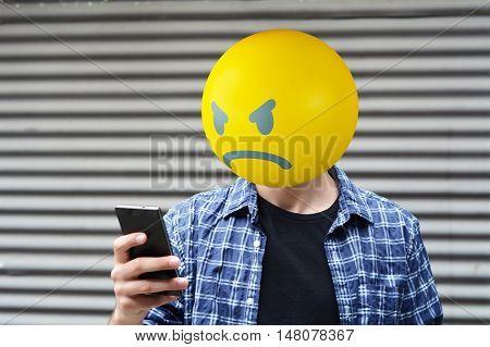 Angry emoji head man using a smartphone.