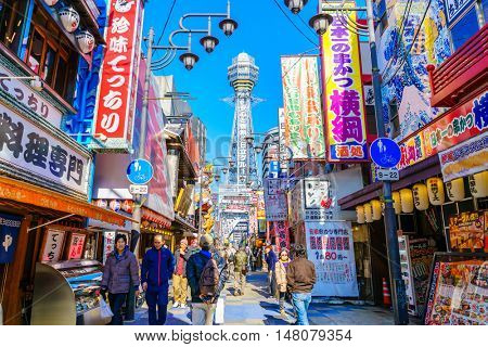 OSAKA, JAPAN - NOVEMBER 30, 2015: Tsutenkaku Tower in Shinsekai (new world) district with blue sky. It is a tower and well-known landmark of Osaka, Japan and advertises Hitachi.